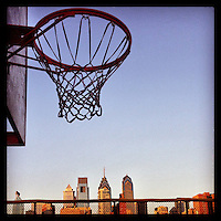A basketball hoop looms above the city skyline at the Marian Anderson Recreation Center just before dusk in south Philadelphia, February 9, 2013.