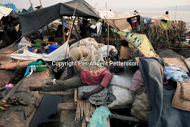 MBANDAKA, DEMOCRATIC REPUBLIC OF CONGO JULY 1: An unidentified man sleeps on a makeshift bed while traveling on a boat made of big trees on the Congo River on July 1, 2006 outside Mbandaka, Congo, DRC. The boat traveled with about 150 passengers from Bumba to Kinshasa, a journey of about 1300 kilometers. The Congo River is a lifeline for millions of people, who depend on it for transport and trade. Passengers slept in the open, with their goats, pigs and other animals. Boat travel is the only option for most people along the river as there?s no roads or infrastructure. Very few can afford to fly in a plane to the capital Kinshasa. During the Mobuto era, big boats run by the state company ONATRA dominated the river. These boats had cabins and restaurants etc. All the boats are now private and are mainly barges that transport goods. The crews sell tickets to passengers who travel in very bad conditions. The conditions on the boats often resemble conditions in a refugee camp. Congo is planning to hold general elections by July 2006, the first democratic elections in forty years. The Congolese and the international community are hoping that Congo will finally have piece and the country will be rebuilt. (Photo by Per-Anders Pettersson)..