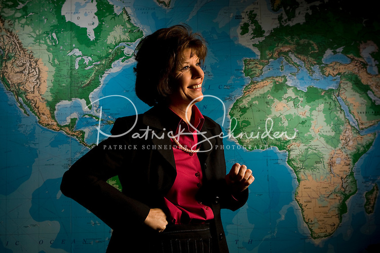 A middle aged woman college professor instructs standing in front of a large world wall map in Belmont, NC.