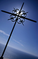 Wrought iron cross facing the sky above the Mediterranean Sea at Cape Corse, Nonza, Corsica, France.