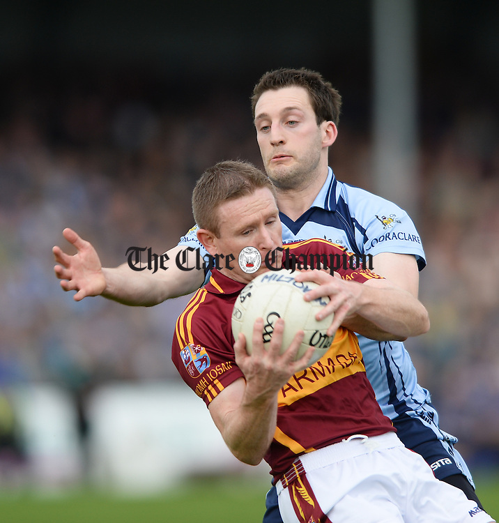 Eoin Curtin of Miltown in action against Thomas Donnellan of Cooraclare during the county senior football final at Cusack park. Photograph by John Kelly.