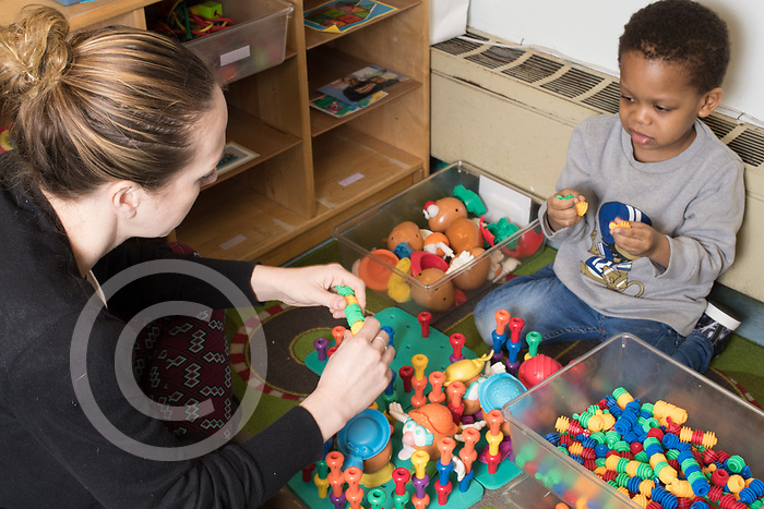 Education Preschool 3 year olds therapist working with boy in classroom