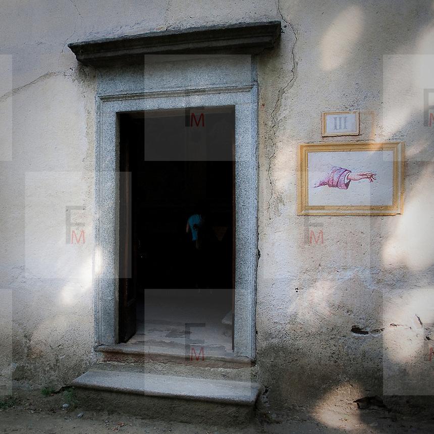 Una mano affrescata sulla facciata di una cappella che indica il percorso devozionale..Sacred Mount of Orta: an hand painted on chapel wall showing the devotional way