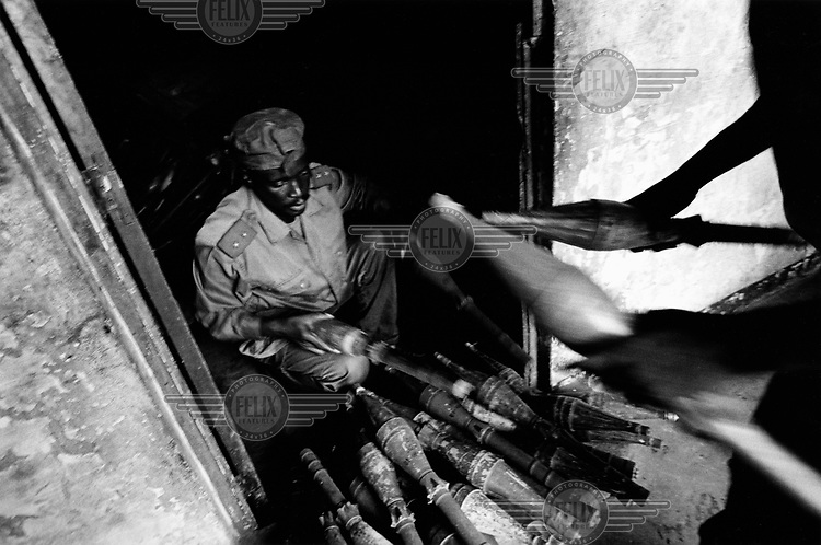 A soldier hands rocket propelled grenades over to Mines Advisory Group (MAG) staff at a large warehouse situated next to a hospital in the town.
