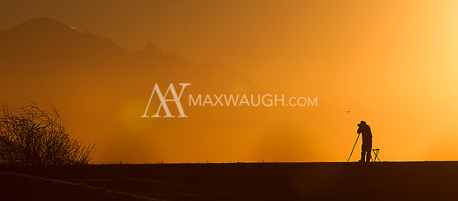 A photographer takes pictures as the sun rises over Boundary Bay.