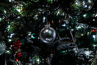 A silver ball Christmas ornament among lights and ornaments on a Christmas tree.