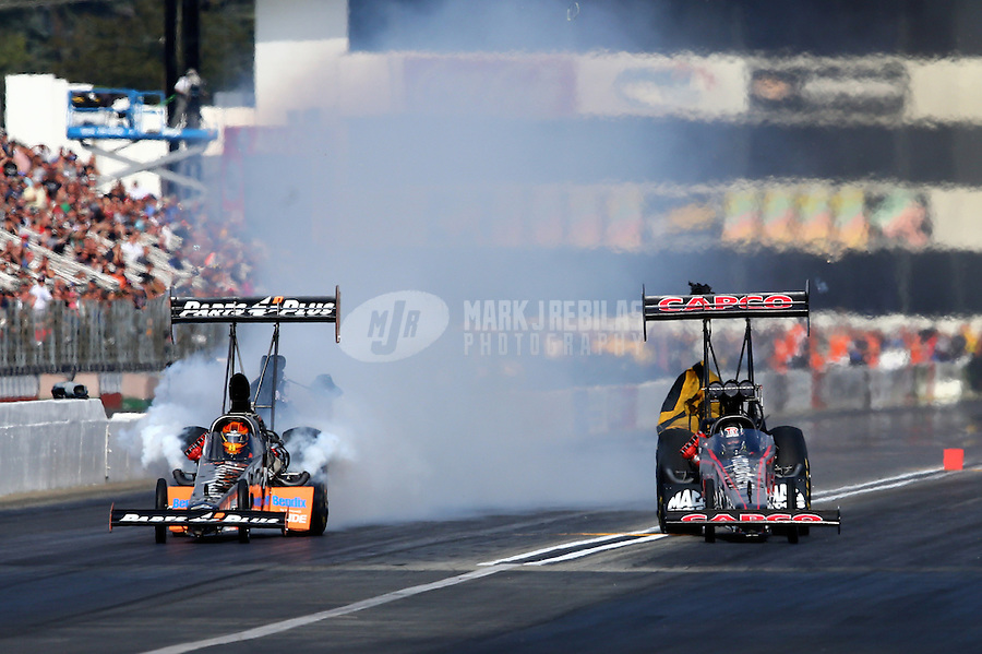 Nov 15, 2014; Pomona, CA, USA; NHRA top fuel driver Billy Torrence (right) races alongside Clay Millican during qualifying for the Auto Club Finals at Auto Club Raceway at Pomona. Mandatory Credit: Mark J. Rebilas-USA TODAY Sports