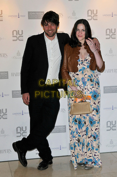 ALEX JAMES & wife.10th Anniversary Party of the Lavender Trust at Breast Cancer Care, .Claridges Hotel, London, England, UK.1st May 2008..full length black suit white shirt brown Temperley leather cropped jacket blue print maxi long dress patterned bag.CAP/PL.©Phil Loftus/Capital Pictures