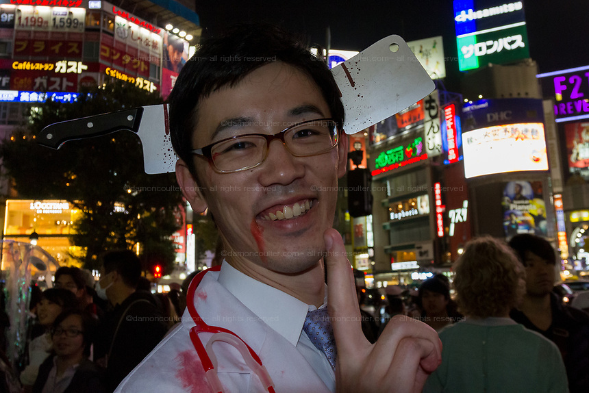 A Japanese man dressed as a doctor with a large knife through his head during the Halloween celebrations Shibuya, Tokyo, Japan. Saturday October 27th 2018. The celebrations marking this event have grown in popularity in Japan recently. Enjoyed mostly by young adults who like to dress up, drink , dance and misbehave in parts of Tokyo like Shibuya and Roppongi. There has been a push back from Japanese society and the police to try to limit the bad behaviour.