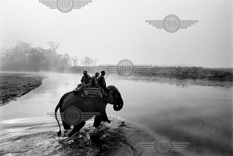 A small group of Royal Nepalese soldiers riding elephants patrol the Royal Chitwan National Park (RCNP) at dawn.