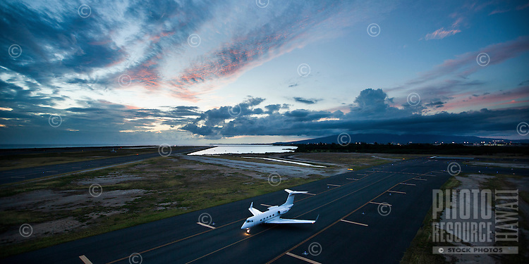 An aerial view of a private jet at sunset at the Honolulu International Airport on O'ahu.