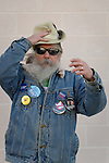"Merrick, New York, USA. October 23, 2016. FRED S. CHANDLER, 66, of North Bellmore, wearing several political campaign buttons supporting Democratic presidential candidate Hillary Clinton, holds on to his hat blown by wind during rally to demand public water and stop New York American Water (NYAW) rate hike. On denim jacket were buttons for Hofstra University DEBATE 2016 - and ""So My Daughter Knows She Can Be President. Hillary 16"" - ""TRUMPBUSTERS"" - ""CLINTON KAINE 16"" - and Monopoly Man character with ""NEVER TRUMP"" text."