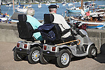 Two elderly people in mobility vehicles, River Deben, Woodbridge, Suffolk, England