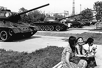 Kazakhstan. Semipalatinsk. A group of young teenagers girls sit on a bench at the Museum of Army. (L) T34 soviet tank from World War II and a row of other tanks from the former Soviet Union. Semey is the kazak name for Semipalatinsk and is located in the Eastern Kazakhstan Province. © 2008 Didier Ruef
