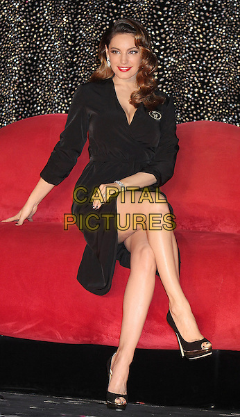 Kelly Brook .Photocall to announce her one week stint in 'Forever Crazy' at Southbank, London, England..October 16th 2012.full length black dress sitting legs crossed cellulite red lipstick peep toe shoes .CAP/PP/MT.©Mickey Townsend/PP/Capital Pictures.