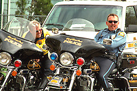 Cops resting on parked motorcycle among official vehicles at Cinco de Mayo festival.  St Paul Minnesota USA
