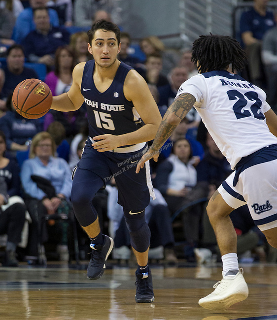 Utah State guard Ben Fakira (15) brings the ball up the court against Nevada in the second half of an NCAA college basketball game in Reno, Nev., Wednesday, Jan. 2, 2019. (AP Photo/Tom R. Smedes)