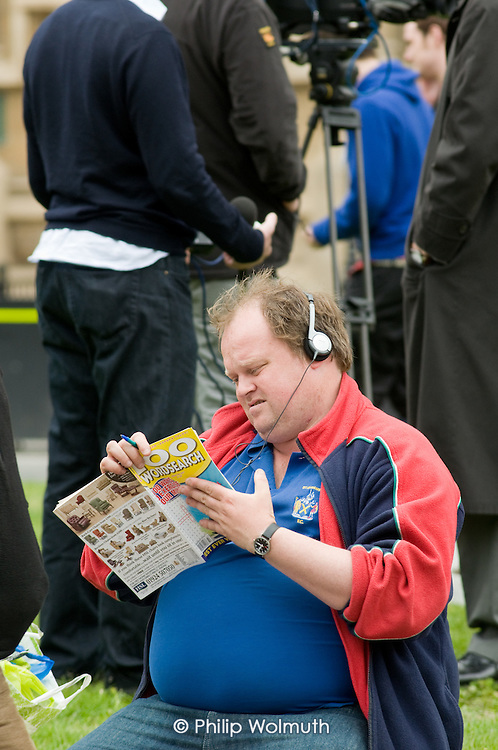 A TV sound technician passes the time on College Green, Westminster, as politicians from the three main parties negotiate following an indecisive result in the 2010 General Election.
