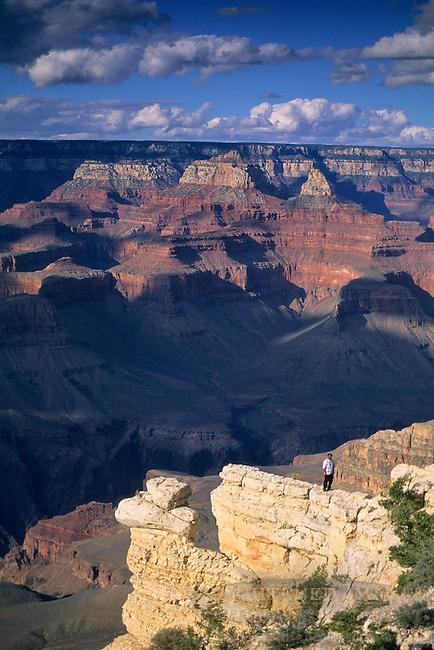 Tourist standing on rock ledge, at Yavapai Point, South Rim, Grand Canyon National Park, Arizona