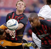 The MetroStars' Eddie Pope heads a ball clear as teammates goalkeeper Jonny Walker and Jeff Parke collide. The New England Revolution were defeated by the MetroStars 3 to 2 on Saturday September 11, 2004 at Giant's Stadium, East Rutherford, NJ..