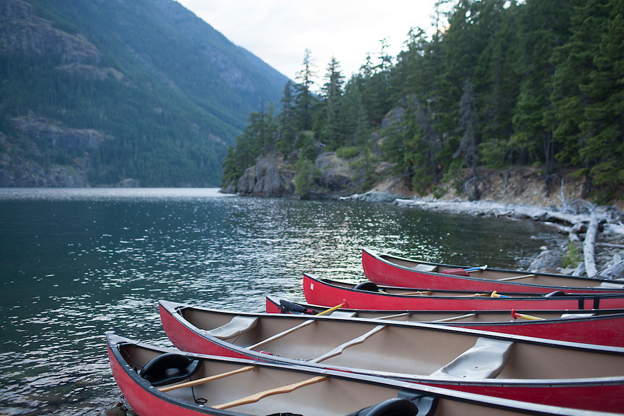 A group of canoes sits on the beach at Ponderosa Campground at Ross Lake, WA, USA.