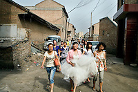Bride Ren Jing and her friends walk toward the mosque for Ren Jing's wedding to Da Fen in Pingliang, Gansu, China.  The newlyweds are members of the Hui ethnic minority, a Muslim ethnic group in northwestern China.