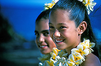 Close-up of the faces of two young hula dancer girls, wearing plumeria leis with an out-of-focus oceanside background