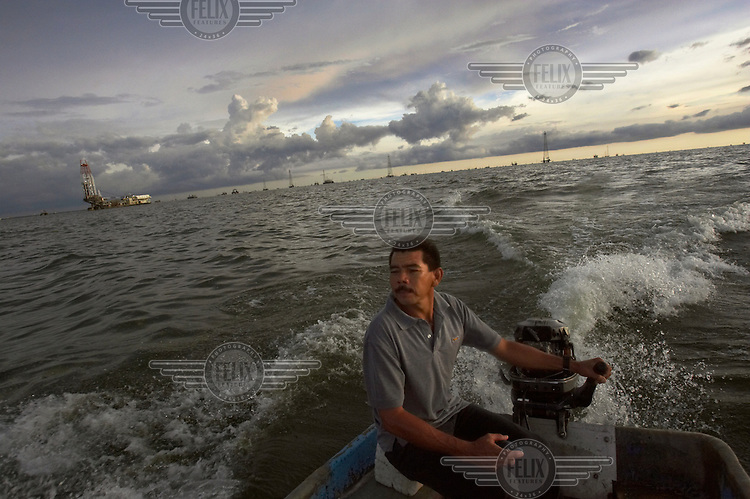 A man drives a boat alongside an installation of the state-owned oil company PDVSA.