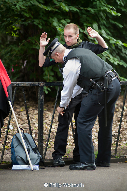 Police search Black Block anarchists in Lincoln's Inn Fields before a demonstration by striking public sector worker over planned pension changes.
