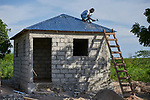 A year after Hurricane Matthew destroyed much of the village of Citerne Remy in Haiti's poverty-wracked northwest, a worker puts the finishing touches on the roof of a new house being built by Church World Service, a member of the ACT Alliance.