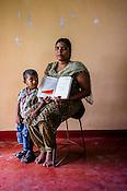 25 year old Rajmohan Srishanthi poses for  photo with her son and CHDR- Child Health Development Record Card (immunization/vaccination card) in Punaineeravi Village in Kilonochchi, Sri Lanka.  Photo: Sanjit Das/Panos
