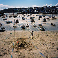 Children make sandcastles on a beach in the harbour surrounded by boats at low tide in St Ives, Cornwall.