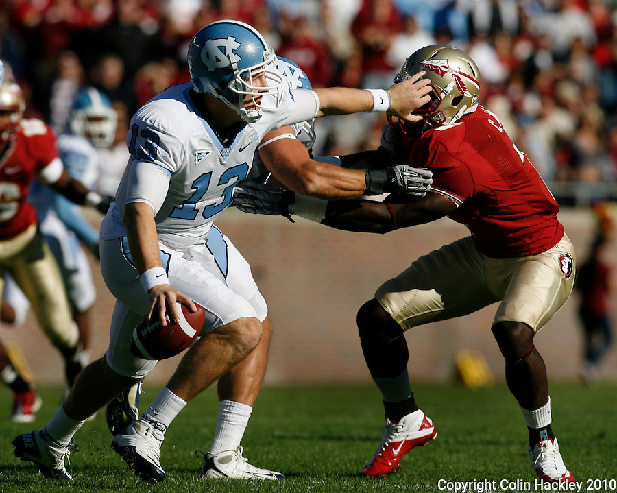 TALLAHASSEE, FL 11/6/10-FSU-NC FB10 CH-North Carolina quaterback T.J. Yates, left, tries to elude Florida State's Christian Jones during first half action Saturday at Doak Campbell Stadium in Tallahassee. The Tar Heels beat the Seminoles 37-35. .COLIN HACKLEY PHOTO