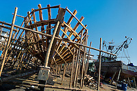 A wooden skeleton of a traditional fishing vessels is seen during the construction process in an artisanal shipyard on the beach in Manta, Ecuador, 8 September 2012. The construction process takes 3-4 months to complete, depending on the ship size and purpose (fish capture methods). Although a wooden boat tends to be more stable on the sea and less expensive to build (up to $0.5 million USD), it needs a maintenance every 2 years, while a fiberglass-made boat, costing almost double the wooden one, may serve 5-6 years without any repairs. The shipyard produces 6-8 vessels every year.