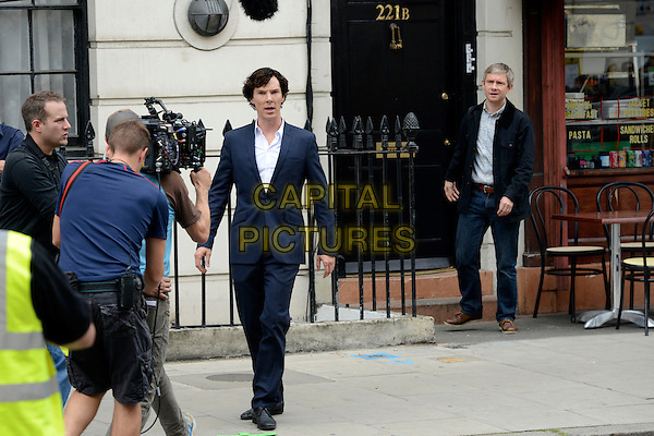Benedict Cumberbatch &amp; Martin Freeman<br /> Filming on the set of &quot;Sherlock&quot;, London, England.<br /> August 21st, 2013<br /> film actor actors acting  full length black suit blue extras 221b door jeans denim jacket camera <br /> CAP/IA<br /> &copy;Ian Allis/Capital Pictures