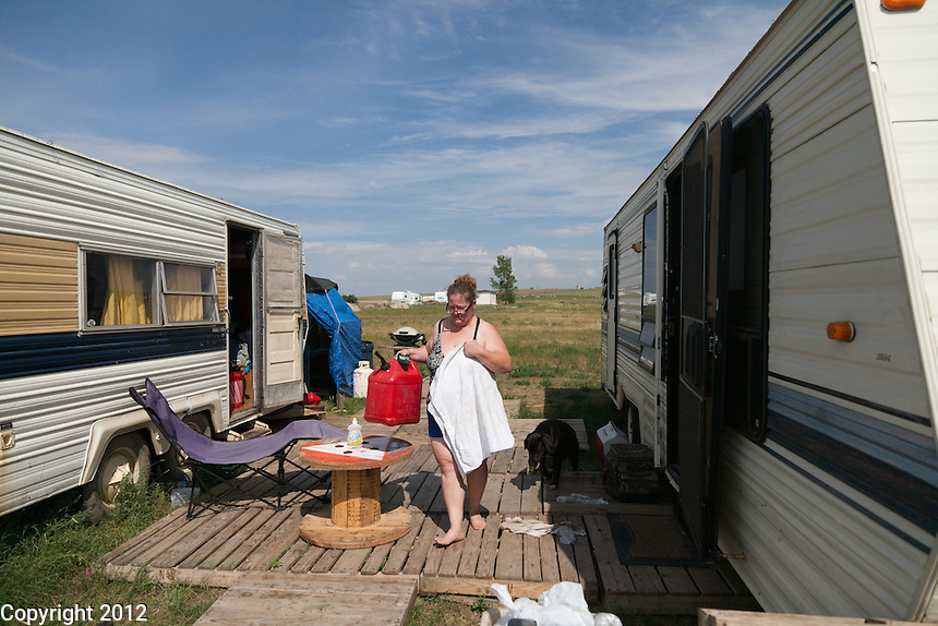 Wendy Bell with gas can to fill the generator to run the TV, and a towel to go to the river.