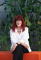 Portrait of interior designer Barbara Hill sitting in the garden of a modern house she designed in Houston, Texas