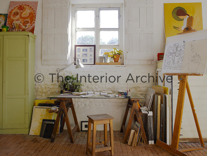 In a corner of the studio a table constructed from antique trestles is situated under a small shuttered window and is piled with sketchbooks