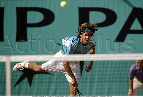GUSTAVO KUERTEN (BRA) serving in his match with Rosset, Men's singles, Round 1, French Open Tennis Championships, Roland Garros, Paris, 030527. Photo: Glyn Kirk/Action Plus...2003 .Man.player players.serve serves.