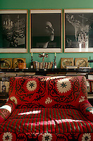 A comfortable armchair in the living room is covered in an antique susani and stands against a wall with a photographic triptych by Bill Henson