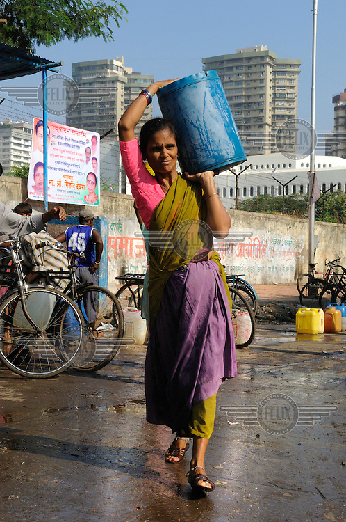 Slum dweller collecting water from a public supply point in Cuffe Parade district in South Mumbai, which is also home to some of the city's most exclusive residential blocks, visible behind.