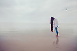 Girl with long hair standing on the ocean/beach reflecting herself in the water and the mist.