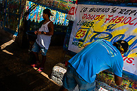 """Colombian sign painters work on a large music party poster in the sign painting workshop in Cartagena, Colombia, 14 April 2018. Hidden in the dark, narrow alleys of Bazurto market, a group of dozen young men gathered around José Corredor (""""Runner""""), the master painter, produce every day hundreds of hand-painted posters. Although the vast majority of the production is designed for a cheap visual promotion of popular Champeta music parties, held every weekend around the city, Runner and his apprentices also create other graphic design artworks, based on brush lettering technique. Using simple brushes and bright paints, the artisanal workshop keeps the traditional sign painting art alive."""
