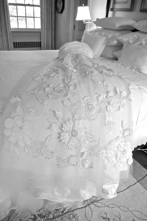 Black & white still life photo of lace bridal gown laid out on bed.