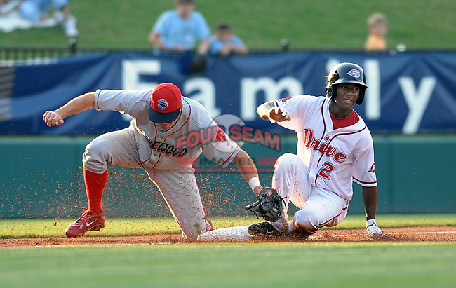 Outfielder WIlfred Pichardo (2) of the Greenville Drive slides safely into third base with his second steal of the inning in a game against the Lakewood BlueClaws on May 13, 2010, at Fluor Field at the West End in Greenville, S.C. Applying the late tag is BlueClaws third baseman Adam Buschini (26).