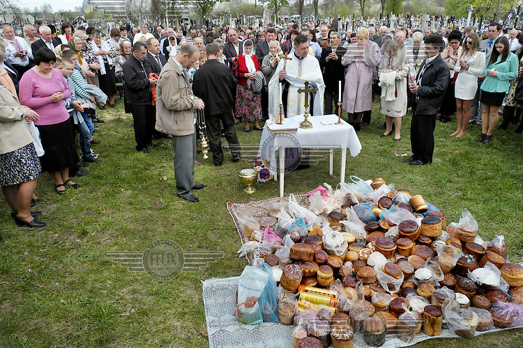 Churchgoers at an Easter Monday open air mass surround a priest and a pile of Easter bread (Paska). The people pay respects to the dead with flowers and prayers.