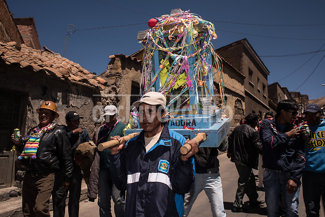 """Group of miners carry their Tata Kajchu (Saint of the mine) to the Cathedral to be blessed, in this case a statue of the Virgin Mary. Potosi, Bolivia. 23 January 2016. With this blessing, they begin the festivities of the Miners Carnival./ Grupo de mineros llevan a su Tata Kajchu (santo de la mina) a la catedral para su correspondiente bendición, en este caso una estatua de la Virgen María. Potosí, Bolivia. Enero 23 de 2016. Con esta bendicion empiezan las fiestas del Carnaval Minero. The customs and beliefs of Andean people are a hybrid of catholic religion and old beliefs. One of its highest expressions is within the Bolivian mining culture that worships the Pacha Mama (Mother Earth), the Celestial Divinity personified in the Catholic God and """"El Tio"""" of the mine (Satan). To the latter, who rules the underworld, they make offerings with sacrifices of llamas inside the mines to ask for protection in the depths of the mountain and abundant mineral."""