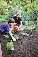 Children planting herb garden in rich soil