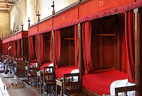 Curtained beds for patients restored in 1875 by Maurice Ourdou, in the Salle des Povres or Room of the Poor, almost 50m long, with a painted wooden ceiling with dragons' heads and caricatures of local people, in Les Hospices de Beaune, or Hotel-Dieu de Beaune, a charitable almshouse and hospital for the poor, built 1443-57 by Flemish architect Jacques Wiscrer, and founded by Nicolas Rolin, chancellor of Burgundy, and his wife Guigone de Salins, in Beaune, Cote d'Or, Burgundy, France. The hospital was run by the nuns of the order of Les Soeurs Hospitalieres de Beaune, and remained a hospital until the 1970s. The building now houses the Musee de l'Histoire de la Medecine, or Museum of the History of Medicine, and is listed as a historic monument. Picture by Manuel Cohen