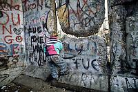 Berlino, 9 Novembre, 1989. Un bambino si arrampica sul muro di Berlino presidiato da soldati della Germania dell'Est poco prima della sua caduta. A youth climbs the Berlin wall.